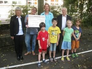 Von links nach rechts: Rektorin Brigitte Debes, Dagmar Kretzinger von Kunterbunt, Doris Füßner vom Elternbeirat, Pfarrer Schindelin; unten: Kinder aus der Steinbachtalschule